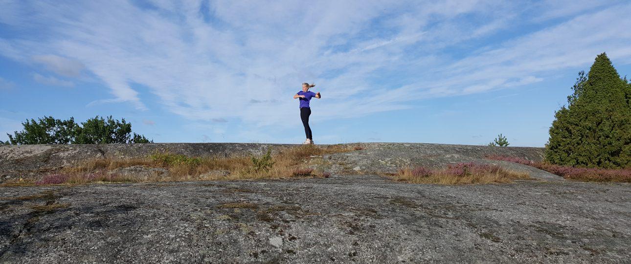 Tjej som joggar bland klipporna