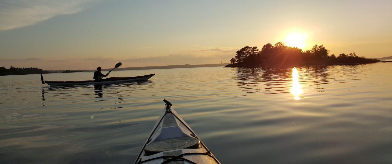 Två kajaker på ett vindstilla vatten väster om Sävö vid solnedgång