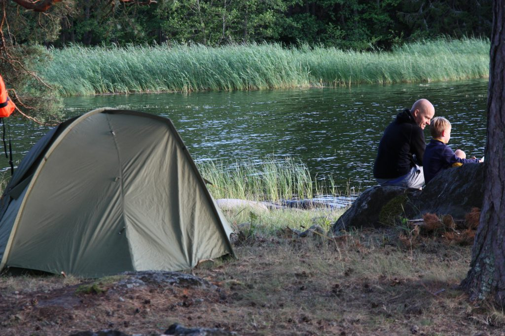 A man and a boy sitting by their tent and the water.