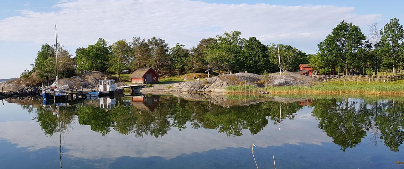 Boholmsviken med brygga och stugan i bakgrunden.